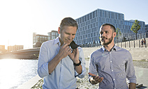 Two businessmen talking at the riverbank - FKF02540