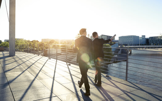 Two businessmen walking on a bridge in the city - FKF02546