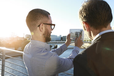 Two businessmen taking a picture with tablet on a bridge in the city - FKF02549