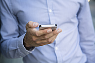 Close-up of businessman holding cell phone - FKF02555