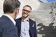 Two businessmen talking at stairs outdoors - FKF02573