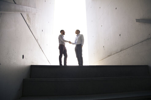 Two businessmen shaking hands in a passageway - FKF02579