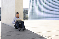 Businessman using laptop outdoors - FKF02582