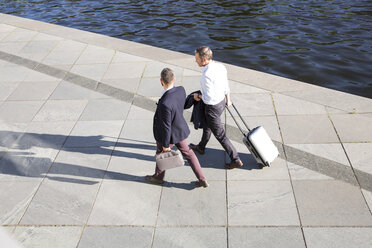 Two businessmen walking and talking at the riverbank - FKF02585