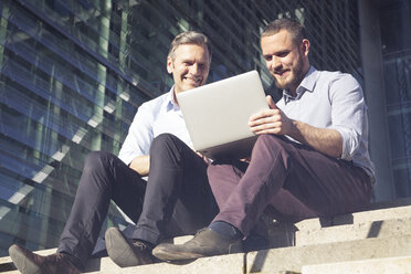 Two smiling businessmen sitting on stairs using laptop - FKF02588