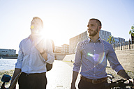 Two businessmen walking with bicycle and skateboard at the riverbank - FKF02591