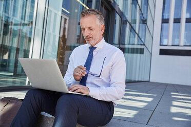 Portrait of businessman using laptop outdoors - SUF00287