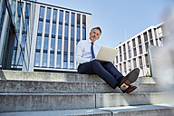 Portrait of businessman sitting on steps using laptop - SUF00290
