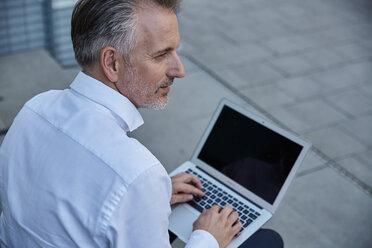 Portrait of businessman using laptop outdoors - SUF00293