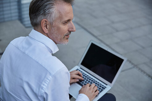 Portrait of businessman using laptop outdoors - SUF00293