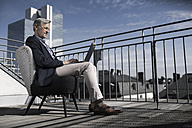 Grey-haired businessman sitting on balcony using laptop - SBOF00733