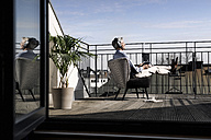 Grey-haired man relaxing in chair on balcony - SBOF00736