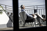Grey-haired man relaxing in chair on balcony listening to music - SBOF00739