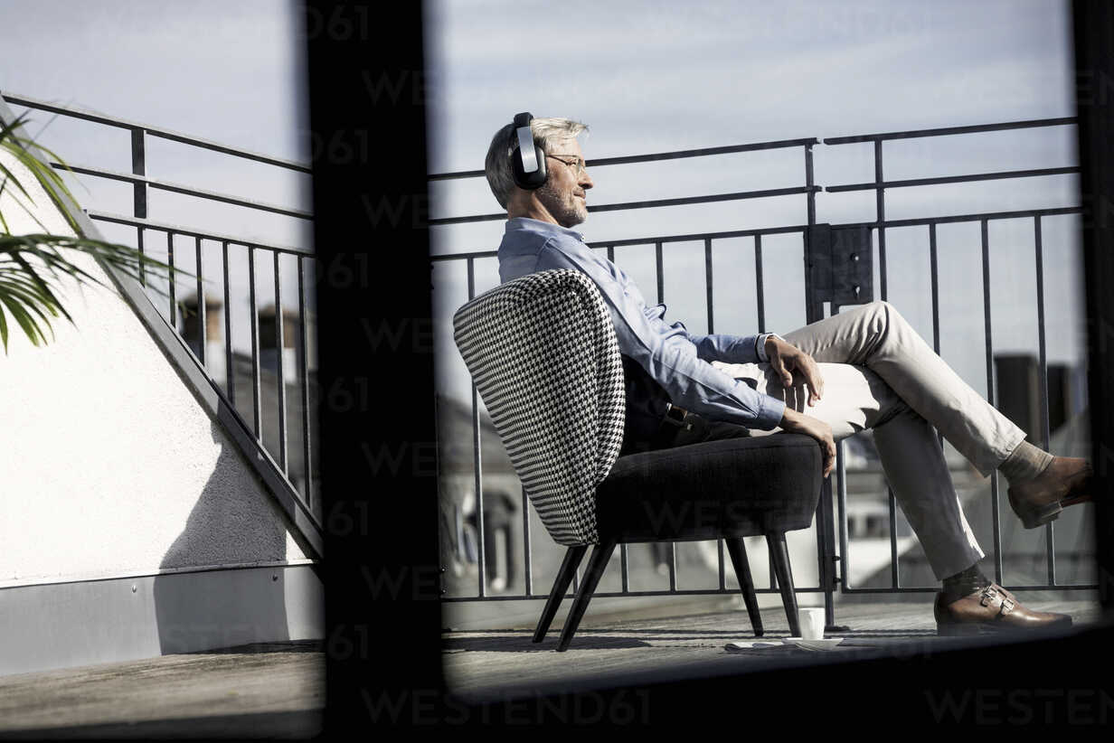 Grey-haired man relaxing in chair on balcony listening to music - SBOF00739 - Steve Brookland/Westend61