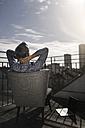 Grey-haired businessman sitting on balcony watching sunset - SBOF00745