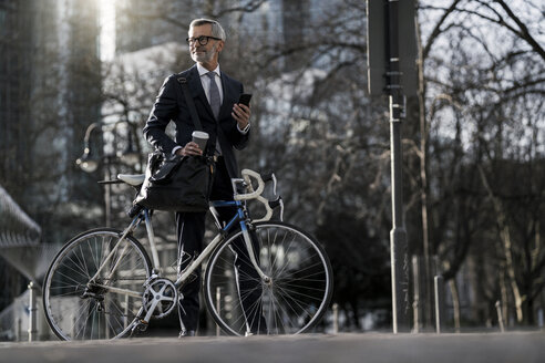 Grey-haired businessman with bicycle and coffee to go in the city - SBOF00748