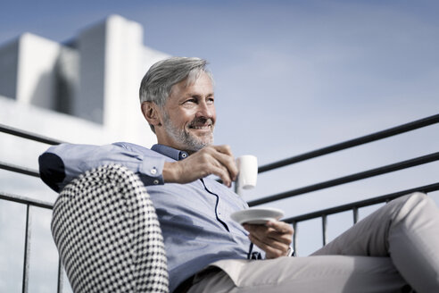 Smiling grey-haired man sitting on balcony and drinking coffee - SBOF00751