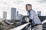 Grey-haired man standing on balcony with newspaper looking over city - SBOF00754