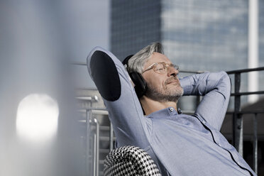 Grey-haired man relaxing in chair on balcony listening to music - SBOF00757