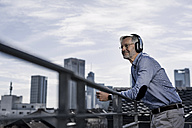 Grey-haired man with headphones enjoying city view - SBOF00760