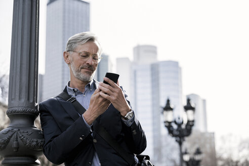 Grey-haired businessman looking at smartphone standing next to street lamp - SBOF00763