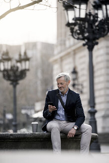 Grey-haired businessman in the city with smartphone and coffee to go - SBOF00766