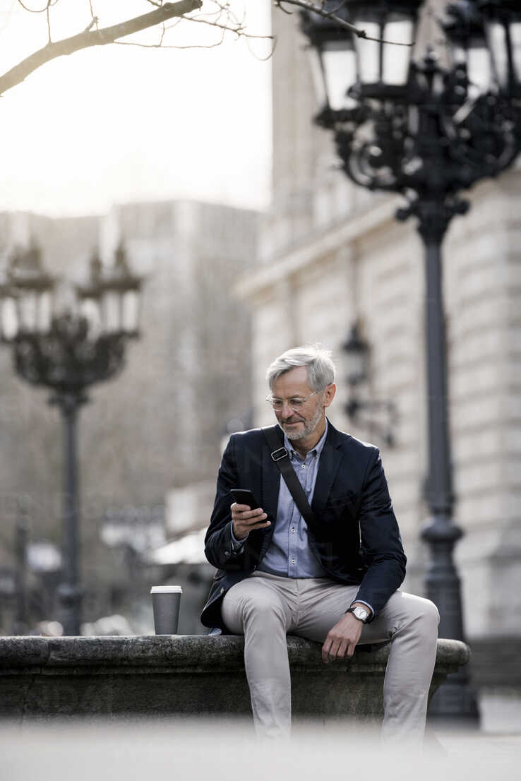 Grey-haired businessman in the city with smartphone and coffee to go - SBOF00766 - Steve Brookland/Westend61