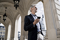 Grey-haired businessman in the city holding smartphone - SBOF00769