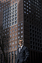 Grey-haired businessman in front of red skyscraper - SBOF00775