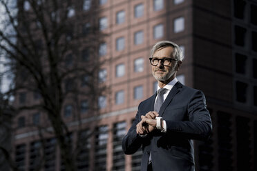 Grey-haired businessman in front of red skyscraper pointing on his smartwatch - SBOF00778