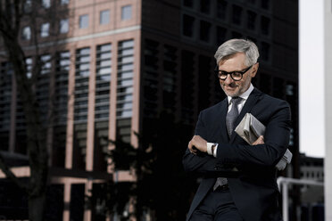 Grey-haired businessman in front of red skyscraper looking at his smartwatch - SBOF00781