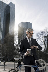Grey-haired businessman with bicycle and coffee to go in the city looking at smartwatch - SBOF00784