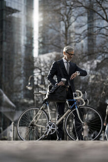 Grey-haired businessman with bicycle and coffee to go in the city looking at smartwatch - SBOF00787