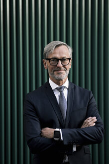 Portrait of confident grey-haired businessman  in front of green wall - SBOF00790