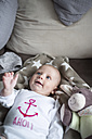 Portrait of smiling baby girl lying on a couch - CSTF01405
