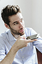 Young businessman working in office, using smartphone - GIOF03252