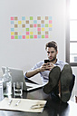 Young businessman working in office, using smartphone - GIOF03258