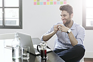 Young businessman sitting at desk with pot of coffee - GIOF03261