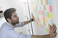 Young businessman working in office with sticky notes on wall - GIOF03282