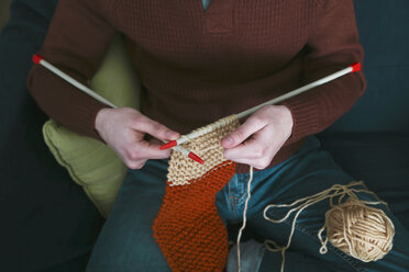 Young man knitting a scarf, partial view - RTBF01007