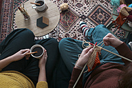 Young couple knitting and having cup  of coffee in living room, top view - RTBF01010