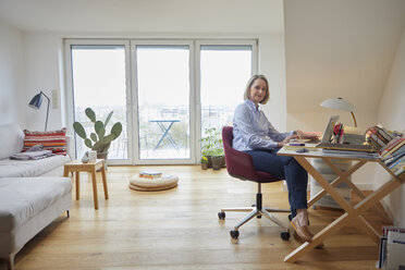 Mature woman at home using laptop at desk - RBF06028
