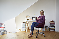 Smiling mature woman at home with laptop at desk - RBF06031
