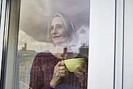 Mature woman holding coffee mug ooking out of window - RBF06034