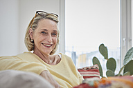 Portrait of smiling mature woman at home on the sofa - RBF06040
