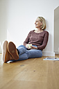 Smiling mature woman at home sitting on the floor - RBF06049