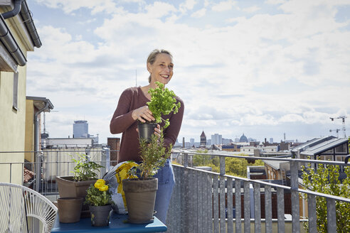 Smiling mature woman caring for plants on balcony - RBF06052
