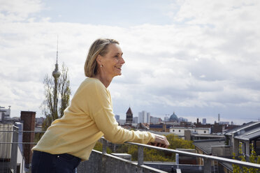 Smiling mature woman on balcony looking at view - RBF06055