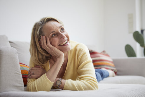 Smiling mature woman at home daydreaming on the sofa - RBF06061