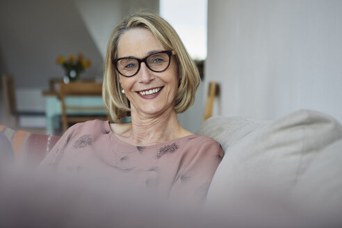 Portrait of smiling mature woman at home on the sofa - RBF06064